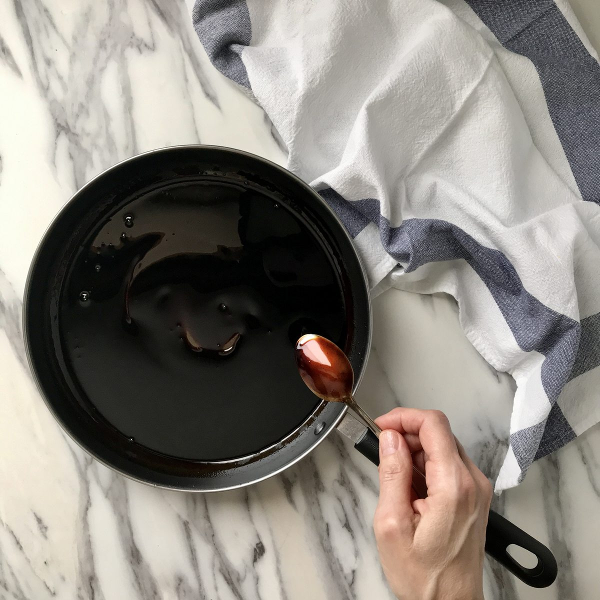 A spoon coated with balsamic vinegar.