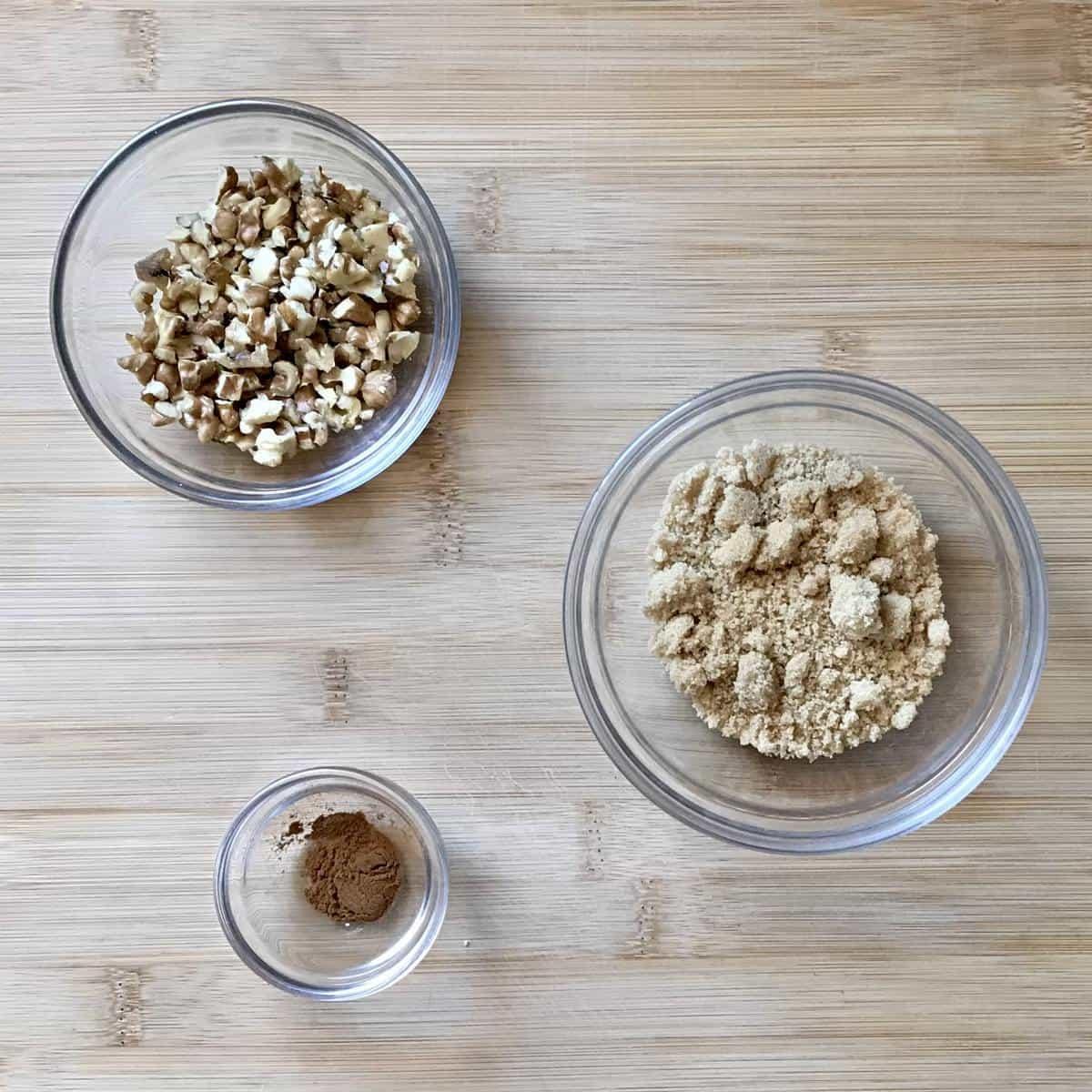 Walnuts, ground cinnamon and brown sugar in individual bowls.