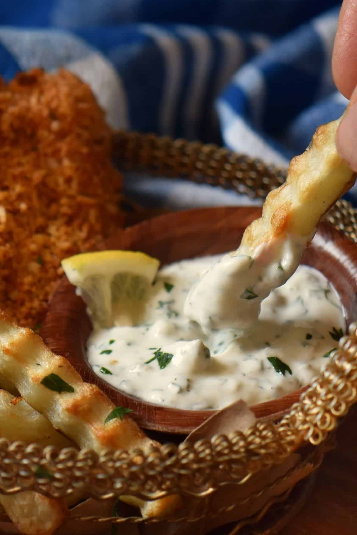 An air fryer crinkle fry dipped into a Greek yogurt sauce without mayo.