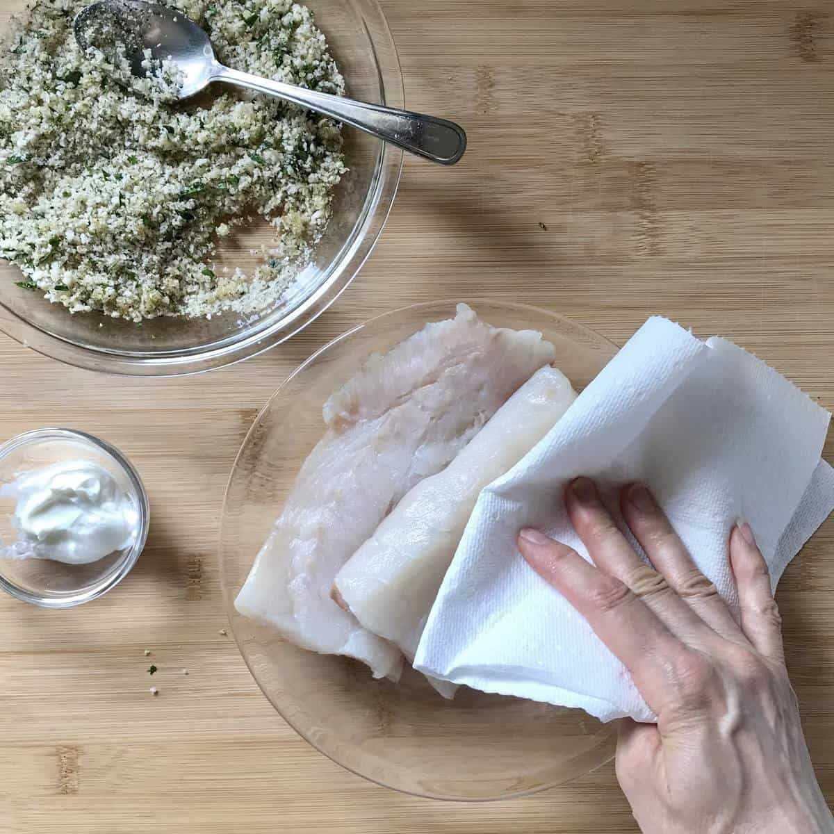 Cod fillets being patted dry with paper towels.