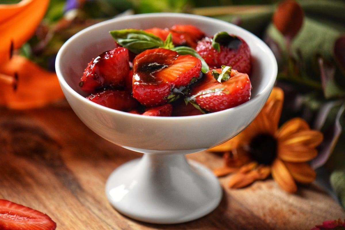Balsamic glazed strawberries in a white dessert bowl.
