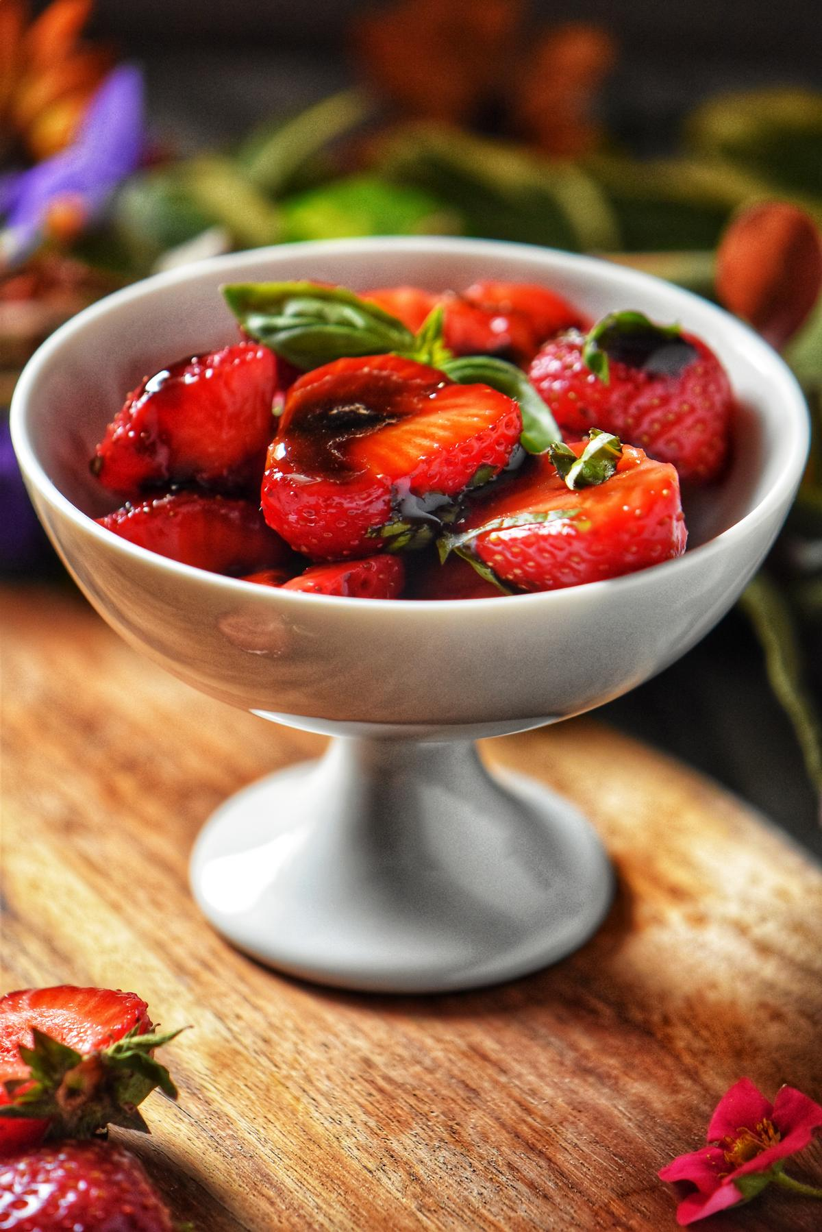 Balsamic strawberries in a white bowl.