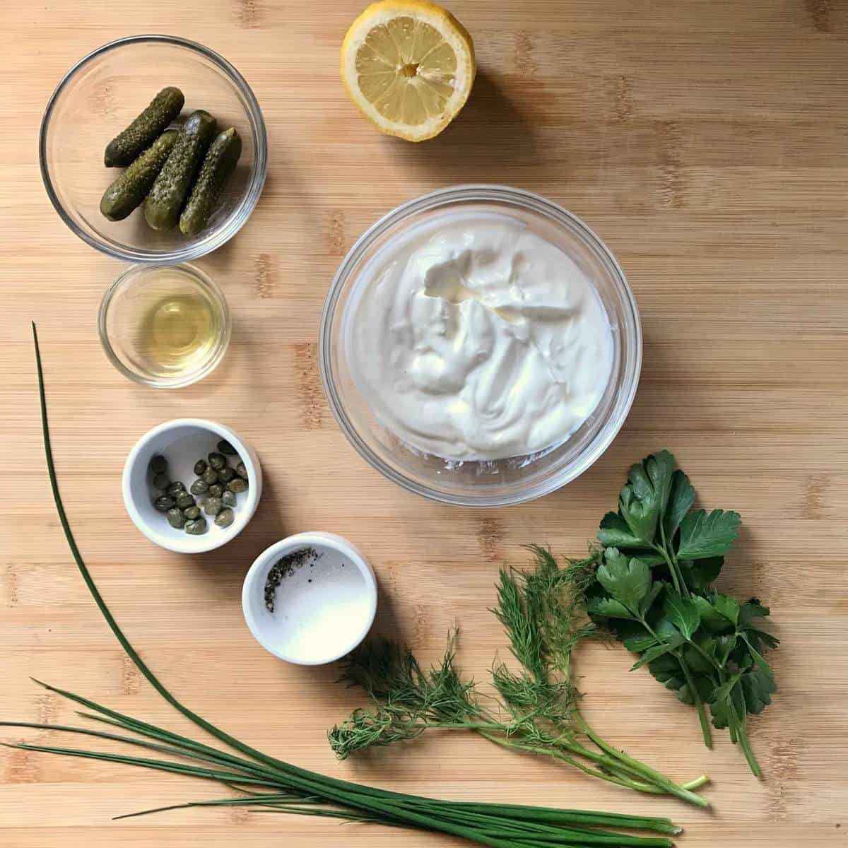 Ingredients to make tartar sauce on a wooden board.