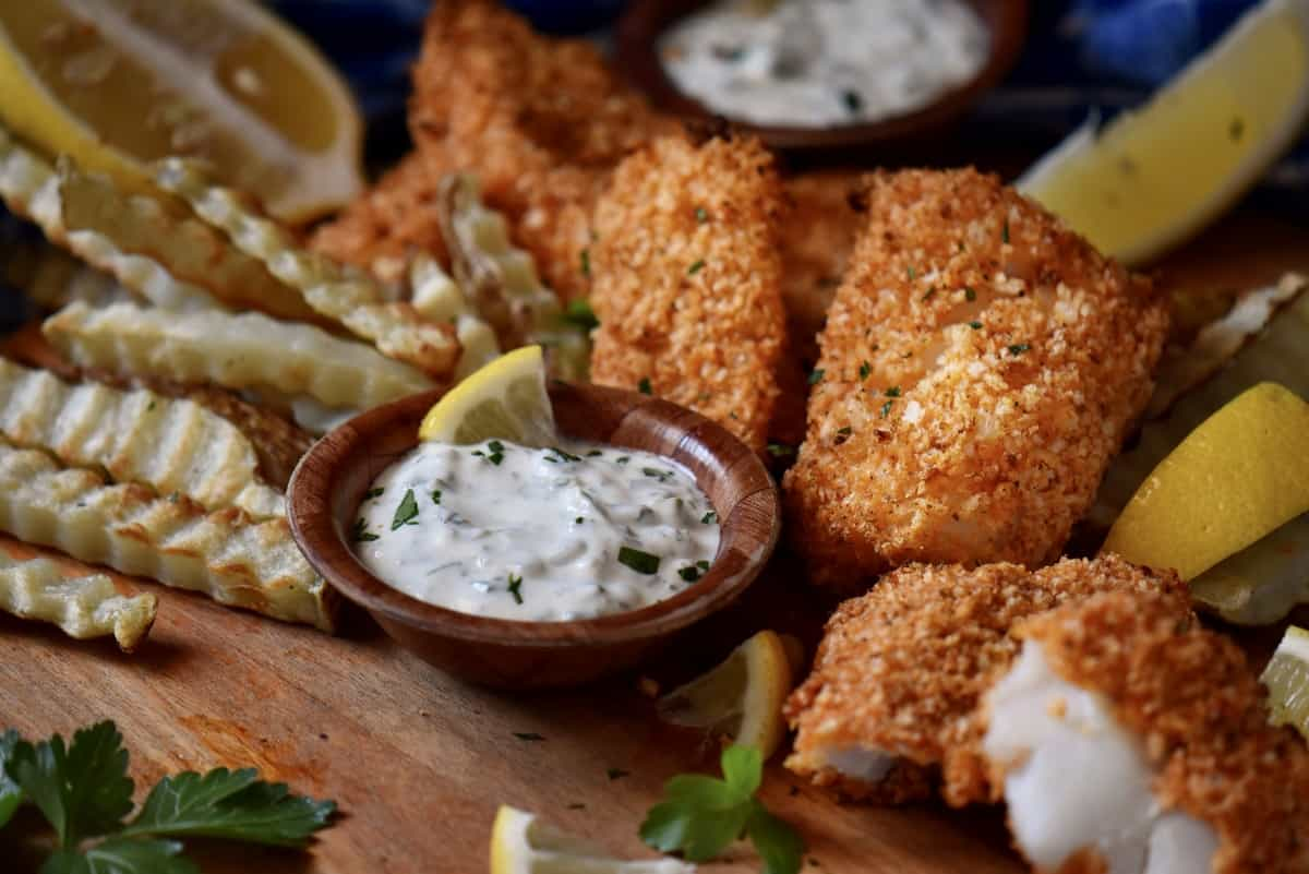 Tartar sauce surrounded by fish and chips.