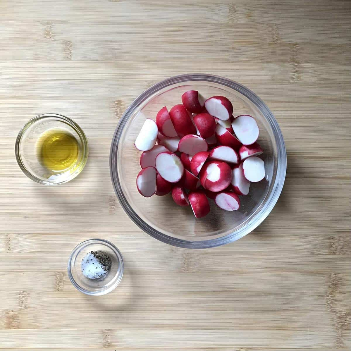 Halved radishes, olive il, salat and pepper in separate bowls.
