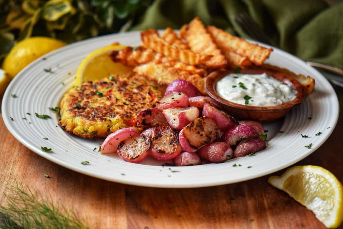 Roasted radishes next to tuna patties on a white plate.