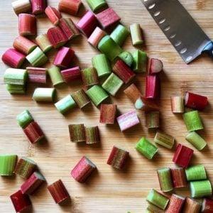 Fresh rhubarb cut into pieces on a wooden board.