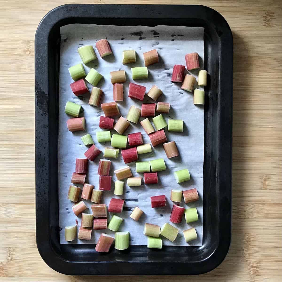 Diced rhubarb on parchment paper on a rimmed pan.