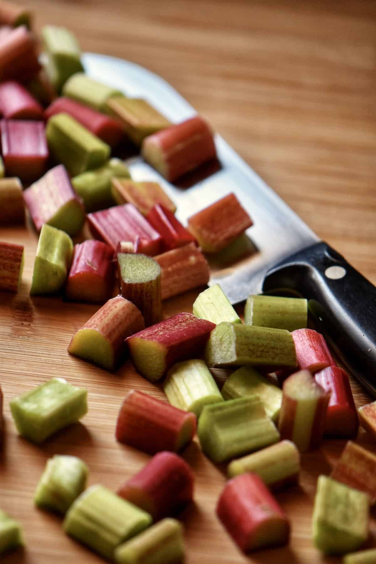 Diced rhubarb on a wooden board, next to a knife.
