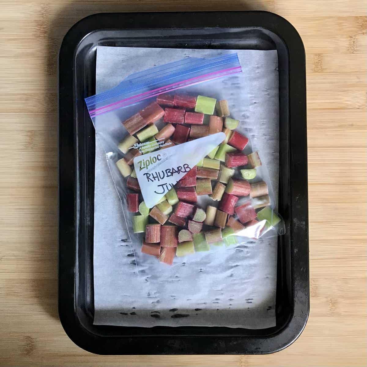 Frozen rhubarb in a Ziploc bag on a baking tray.