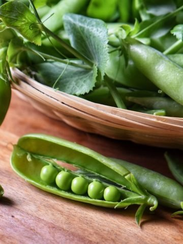 An opened pea shell next to a basket of peas.