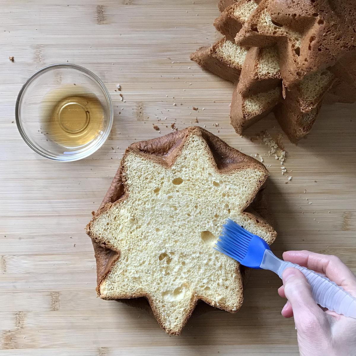 Rum being brushed on the surface of a pandoro cake.