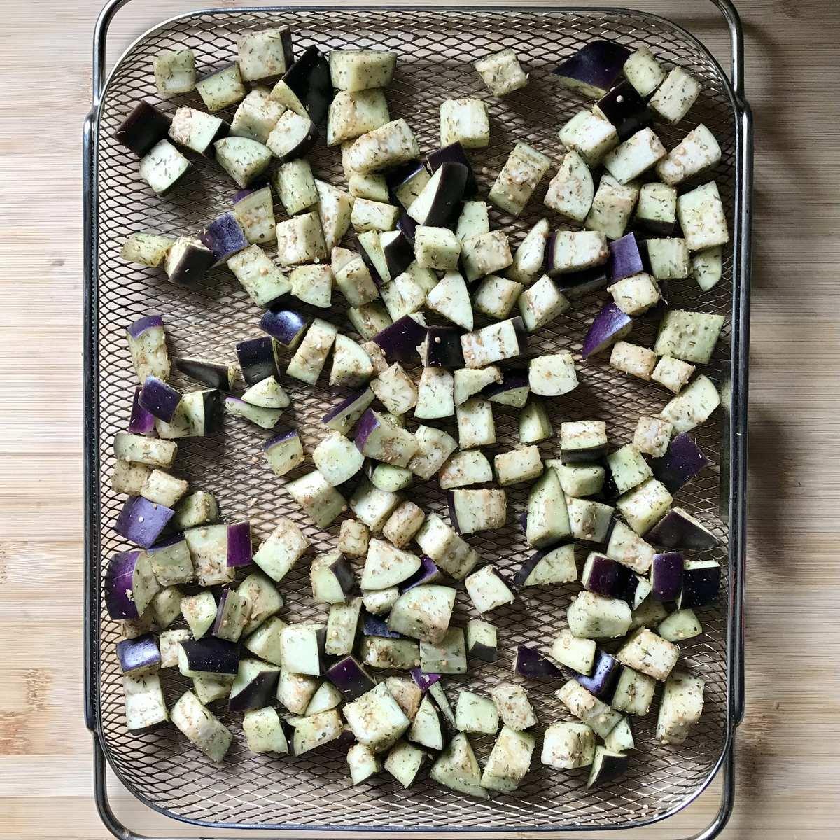 Diced eggplant spread on an air fryer basket.