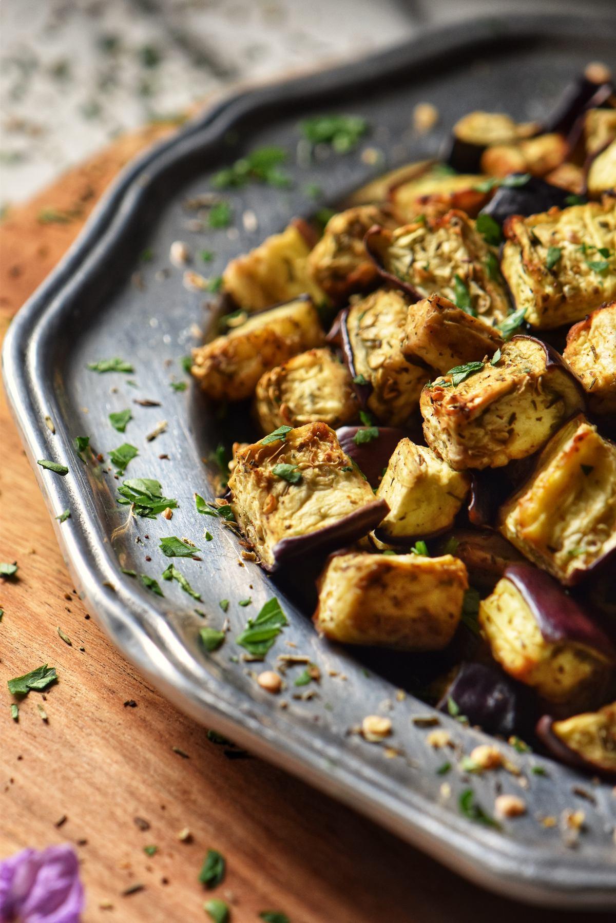 Lightly seasoned eggplant cubes on a silver platter.