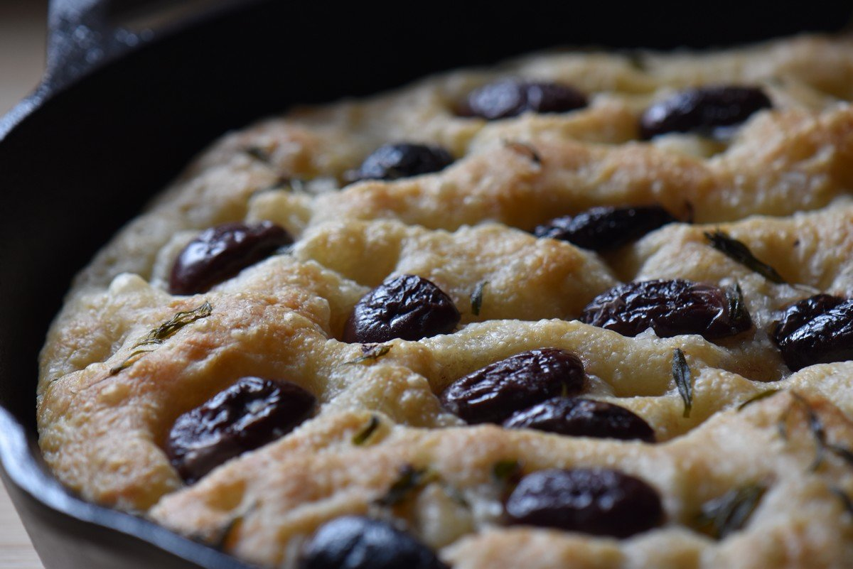 Olive focaccia with thyme in a cast iron skillet.