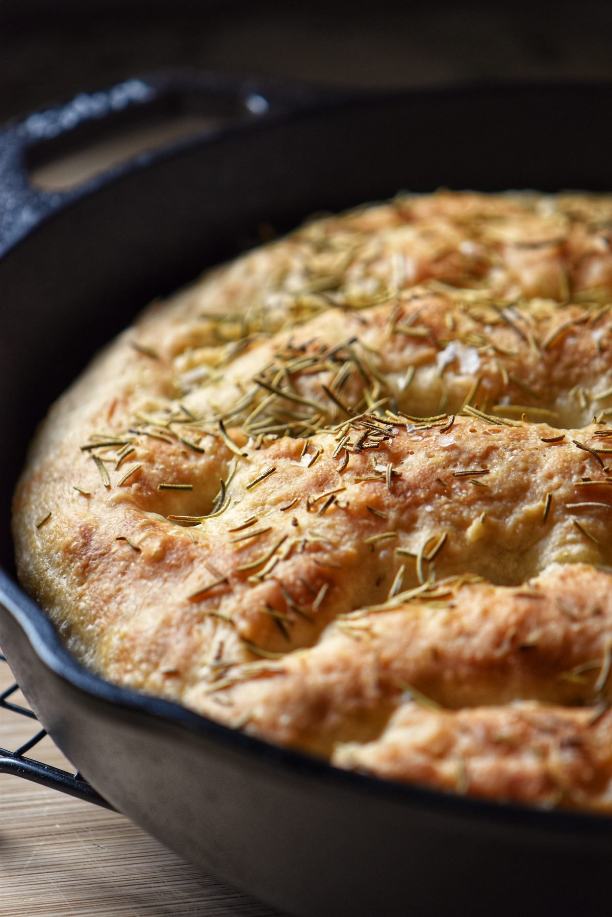 Cast iron focaccia dough garnished with rosemary.