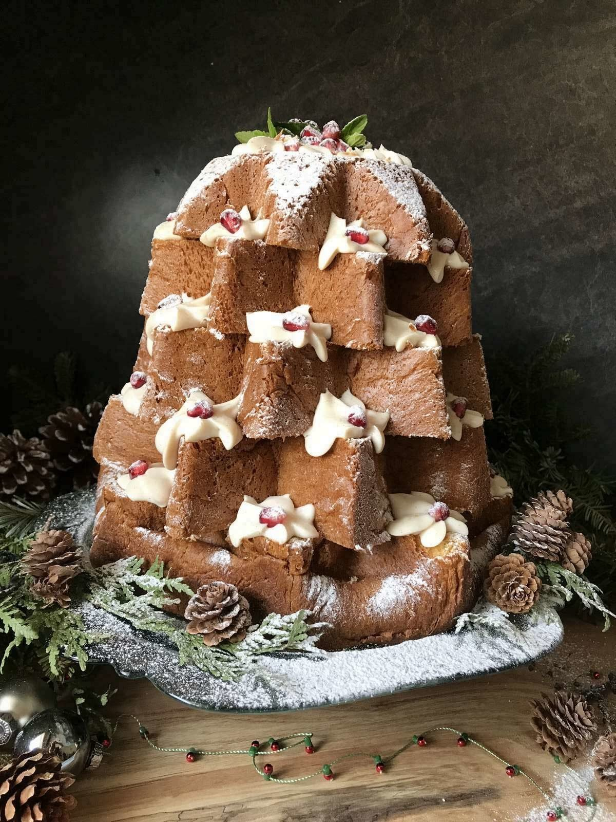 A Pandoro Christmas tree cake garnished with whipped ricotta and icing sugar.