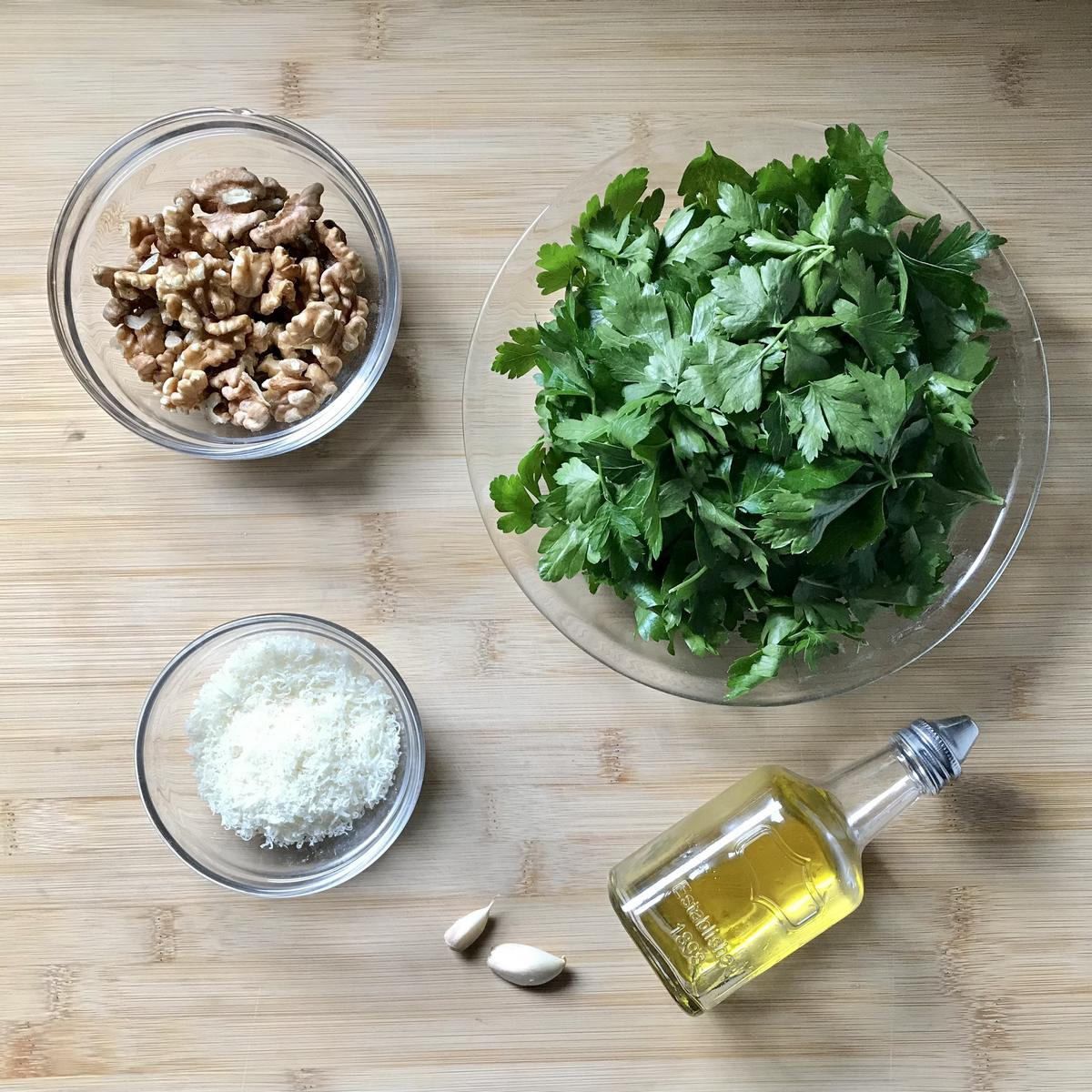 Walnuts, cheese, parsley, garlic and olive oil on a wooden board.