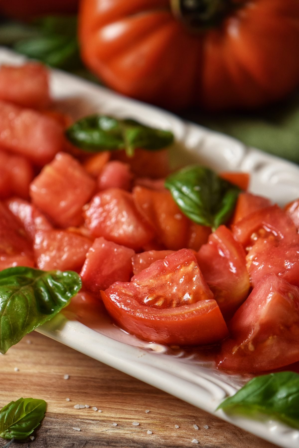 Marinated tomato salad on a white serving platter.