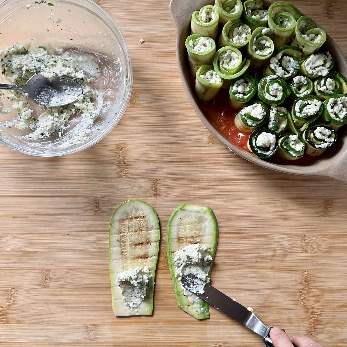 Ricotta filling being spread on grilled zucchini.