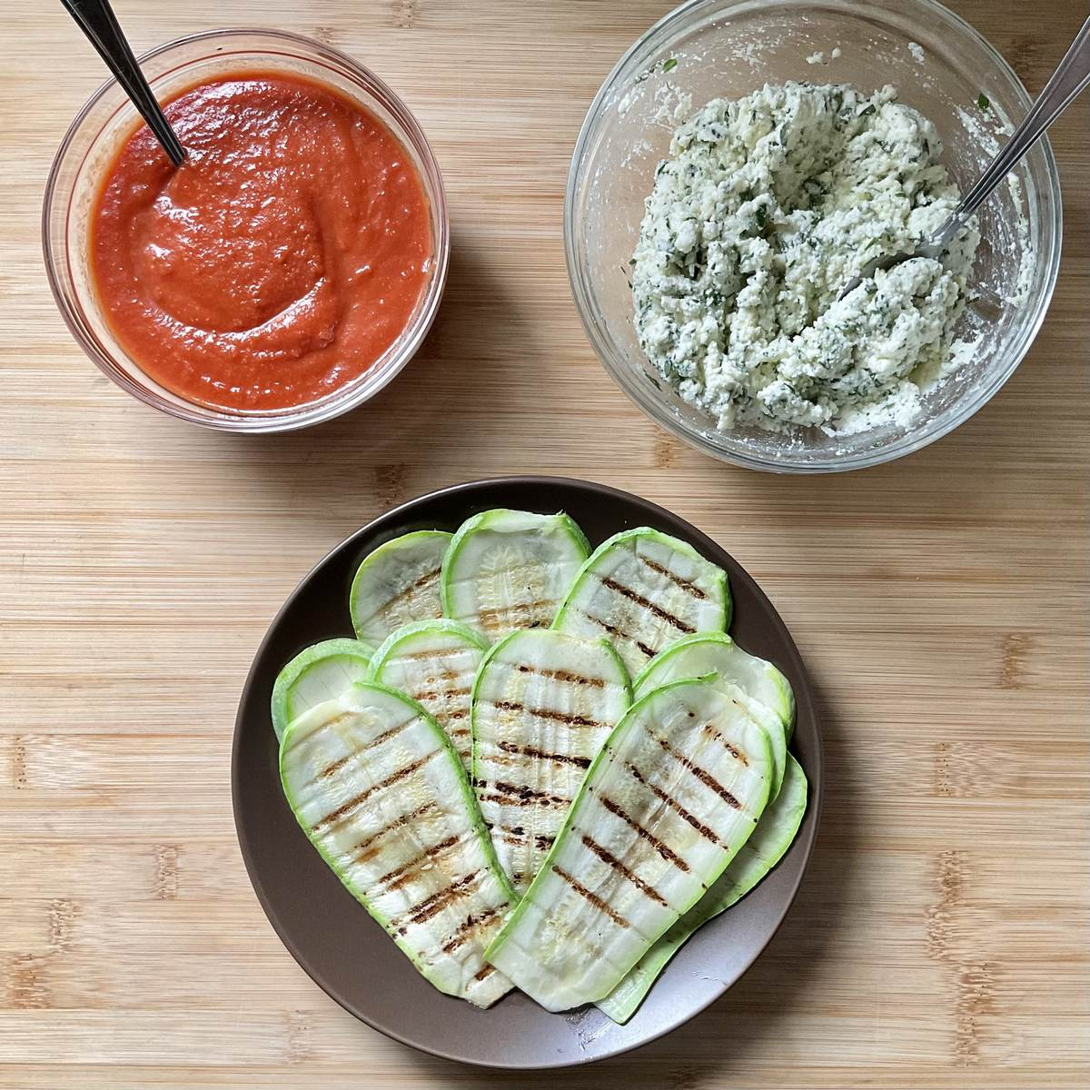 Grilled zucchini, marinara sauce and ricotta filling on a wooden surface.