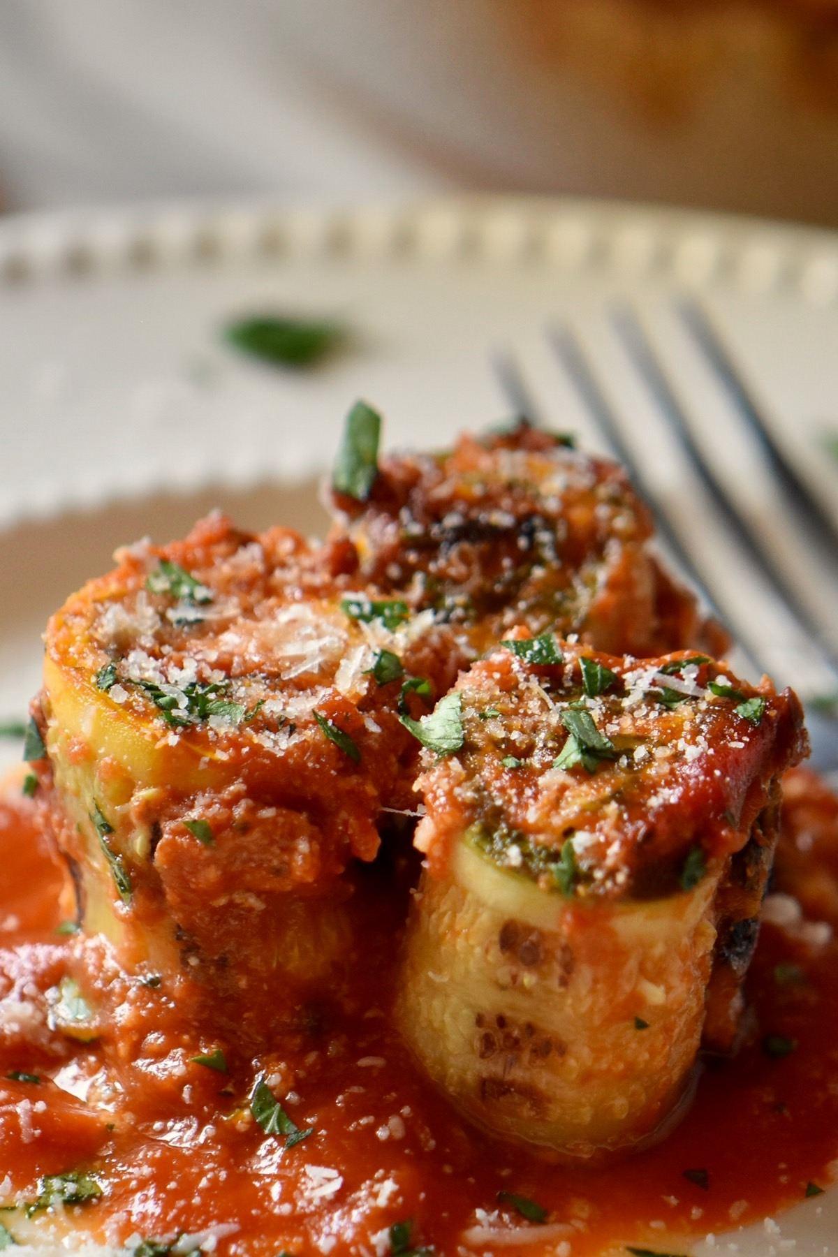 Zucchini lasagna rolls on a white plate.