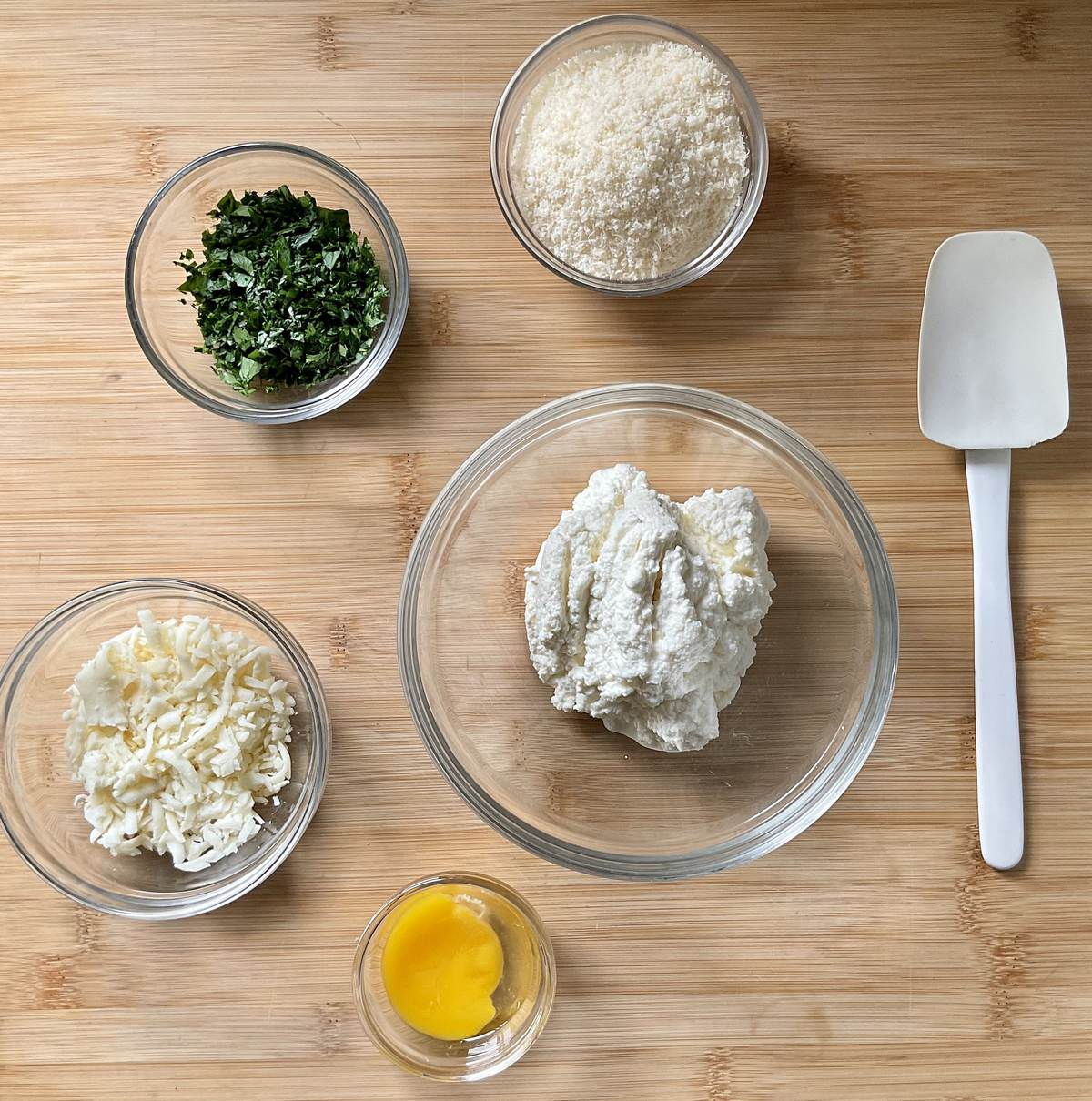 Ingredients to make ricotta filling in separate bowls.