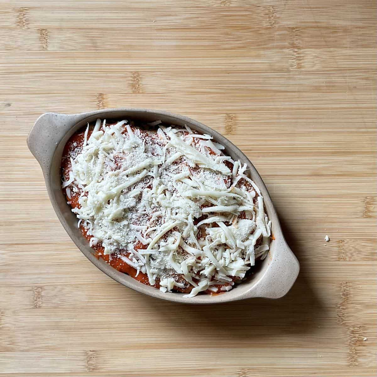 The top layer of eggplant is garnished with grated mozzarella.