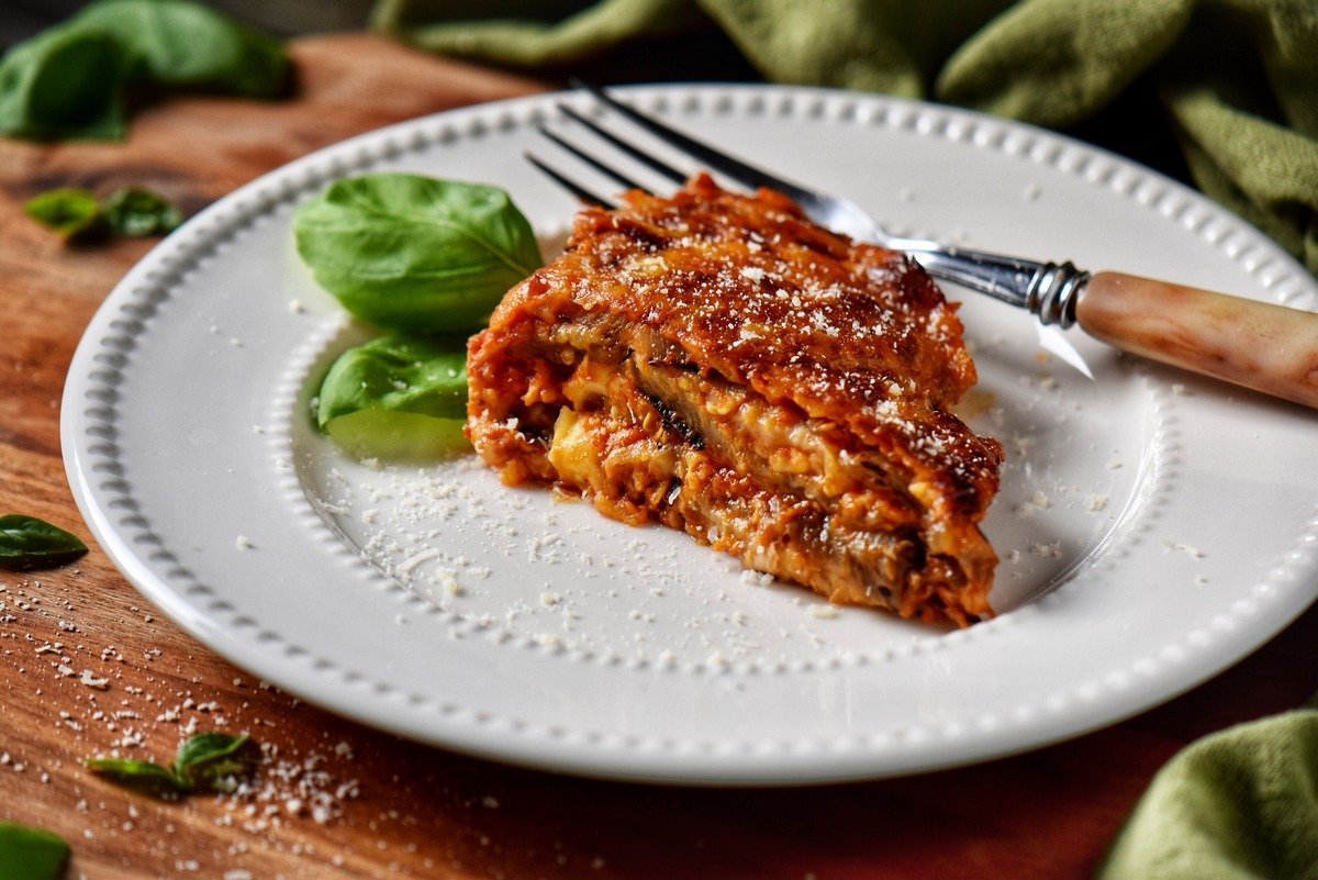 A portion of eggplant parmesan on a white plate.