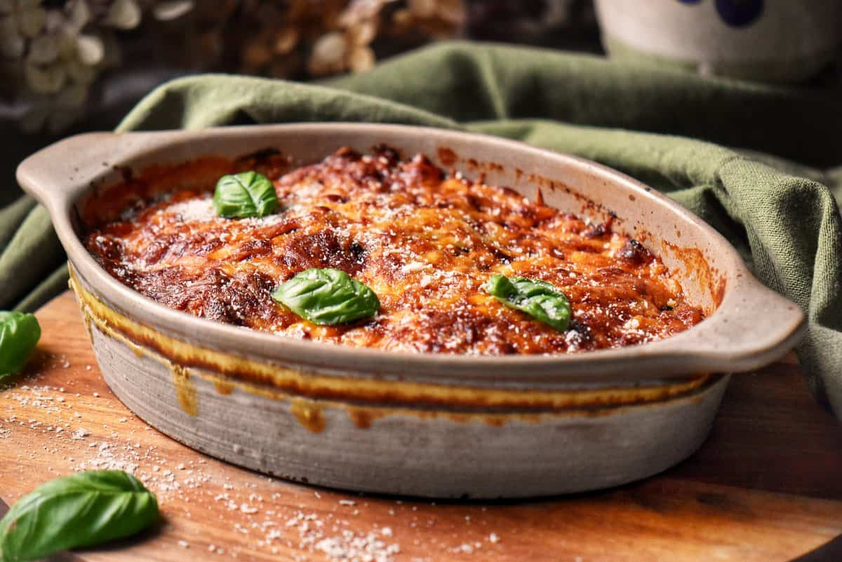 A casserole dish of Eggplant Parmesan garnished with basil leaves.