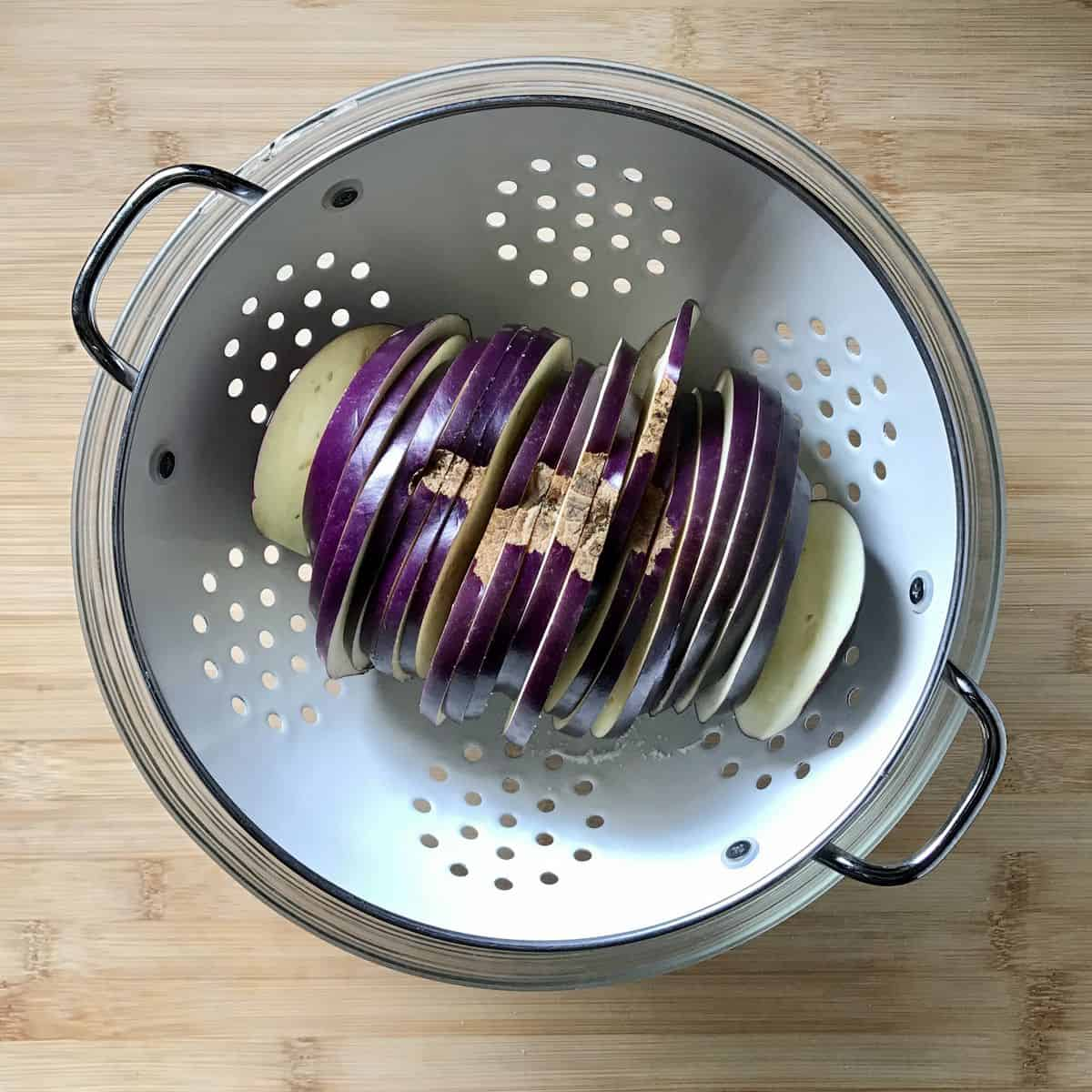 Slices of eggplant in a colander.