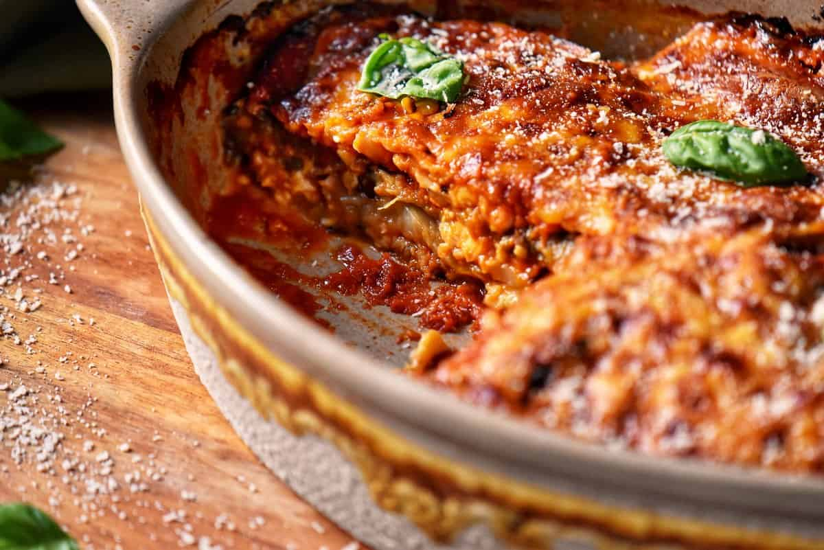 A casserole dish of eggplant parmesan with one portion missing.