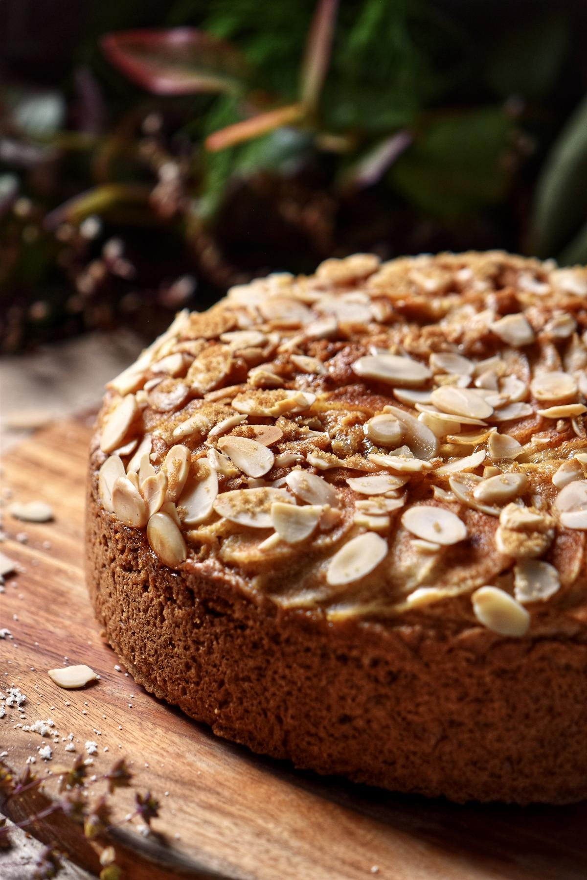 A pear cake garnished with sliced almonds on a wooden board.