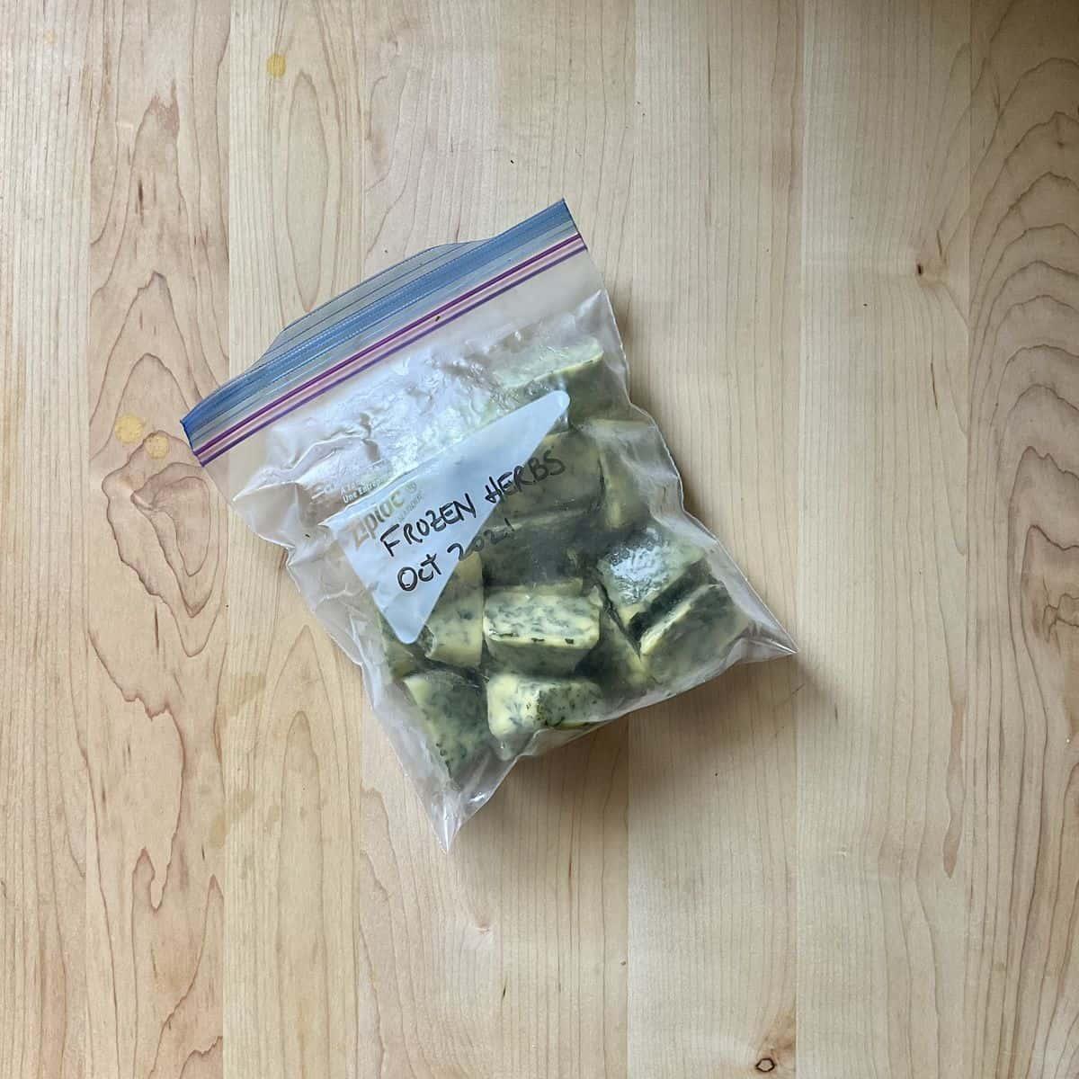 Frozen ice cubes of herbs in a plastic freezer bag.